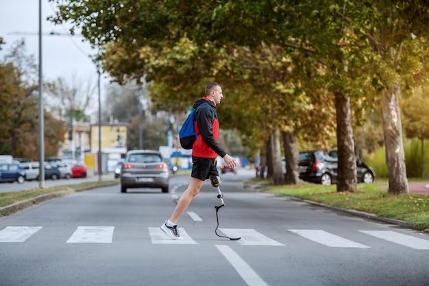 スポーツウェアのハンサムな白人障害者スポーツマンの全長、義足とバックパックの交差道路。