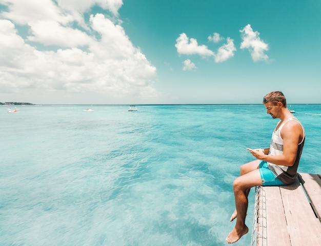 Во всю длину красивого кавказского человека, сидящего на пристани и с помощью смартфона. концепция летних каникул.