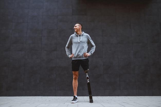 야외에서 어두운 벽 앞 엉덩이에 손으로 인공 다리 서 잘 생긴 백인 웃는 젊은 스포츠맨의 전체 길이입니다.