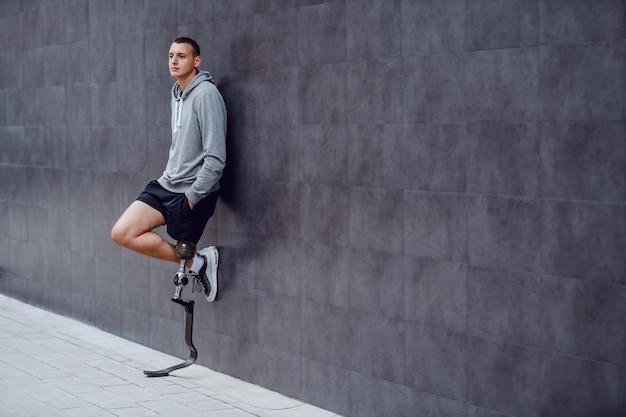 外の壁にもたれて、ポケットに手を持っている義足のハンサムな白人のスポーツマンの完全な長さ。