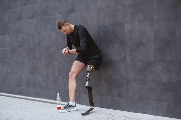В полный рост красивый кавказский спортсмен с искусственной ногой, опираясь на стену, смотрит на наручные часы и отдыхает от бега. рядом с ним бутылка с прохладительными напитками.
