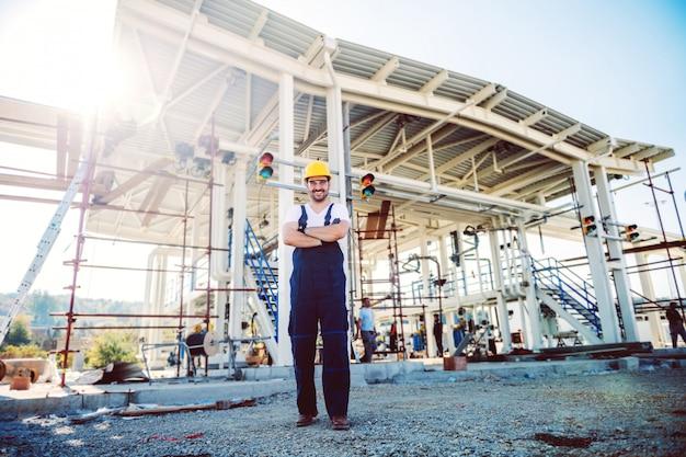 Во всю длину красивого кавказского работника в комбинезоне и шлеме на голове стоя на открытом воздухе со скрещенными руками. добыча нефти.