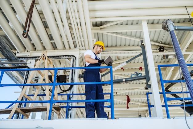 Во всю длину красивого кавказского работника в спецодежде и с шлемом на голове, стоя на нефтеперерабатывающем заводе и с помощью планшета.