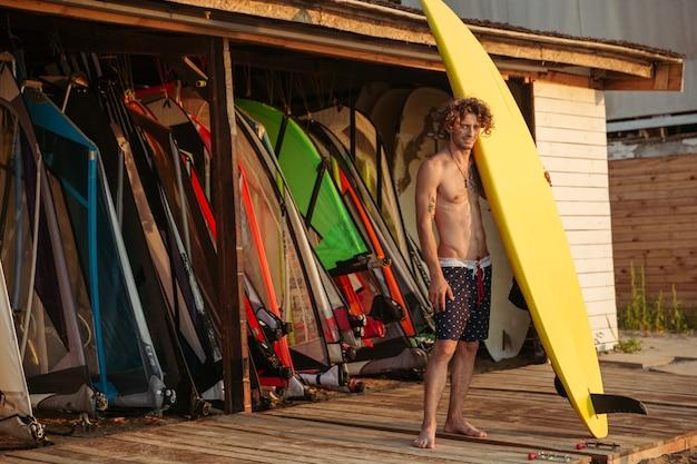 Красивый кудрявый мужчина-серфер в полный рост стоит и держит желтую доску для серфинга