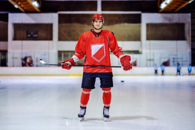 В полный рост красивый хоккеист держит клюшку, стоя на льду в зале