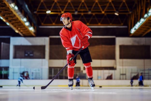 Красивый хоккеист в полный рост катается на коньках, держит клюшку в руках и пытается играть в защите.