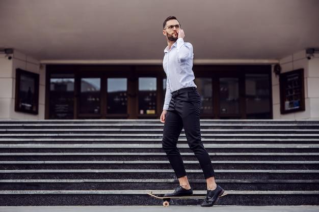 エレガントな服装のハンサムな男の全身がスケートボードに乗り、目をそらしています。