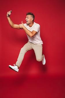 赤で隔離のスマートフォンでジャンプしてselfieを取る縞模様のtシャツのハンサムな男の全長