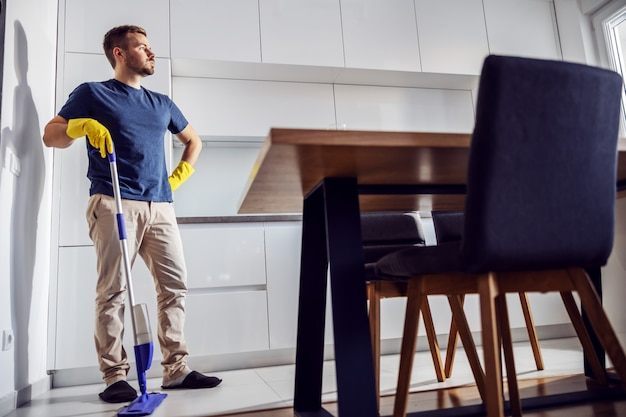 キッチンに立ってモップに寄りかかってハンサムな疲れた男の完全な長さ。きれいにすることがたくさんあります。