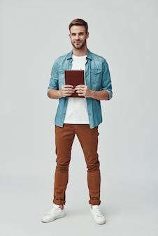 Полный рост красивый молодой человек смотрит в камеру и улыбается, стоя на сером фоне
