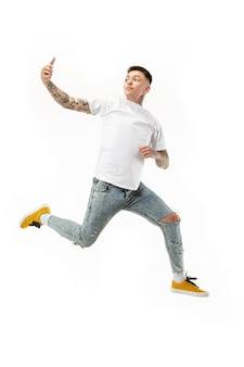 오렌지 스튜디오 배경 점프하는 동안 잘 생긴 젊은 남자 복용 전화의 전체 길이입니다. 모바일, 모션, 움직임, 비즈니스 개념