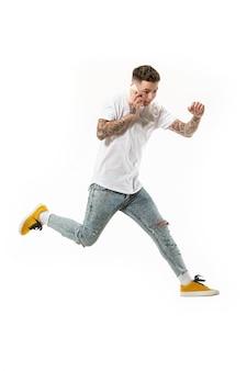 Во всю длину красивый молодой человек принимает телефон, прыгая на оранжевом фоне студии.