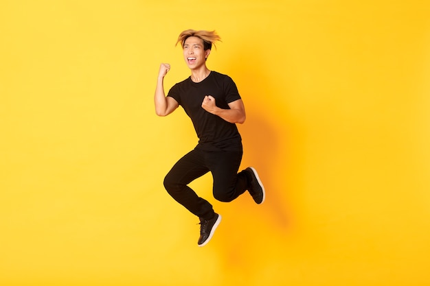 ジャンプして勝利を祝う黒い服を着た幸せな魅力的なアジアの男のフルレングスは、目標を達成し、黄色の壁に立って、勝利します。