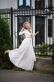 ドレスを着て、柵の近くに立って通りを歩いて幸せな美しい若い女性の完全な長さ。美容とファッションのコンセプト