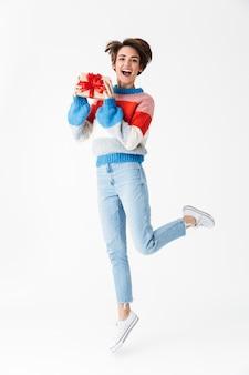 Полная длина счастливая жизнерадостная девушка в свитере прыгает на белом