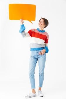 白で隔離の立っているセーターを着て、空の吹き出しを保持している幸せな陽気な女の子の完全な長さ