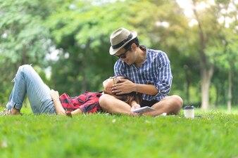Full length of happy female lying on happy man lap in park