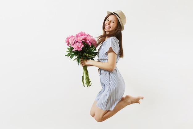 青いドレス、ピンクの牡丹の花の花束を保持している帽子、白い背景で隔離のジャンプの幸せな楽しい若い女性の完全な長さ。聖バレンタインの日、国際女性の日の休日の概念。