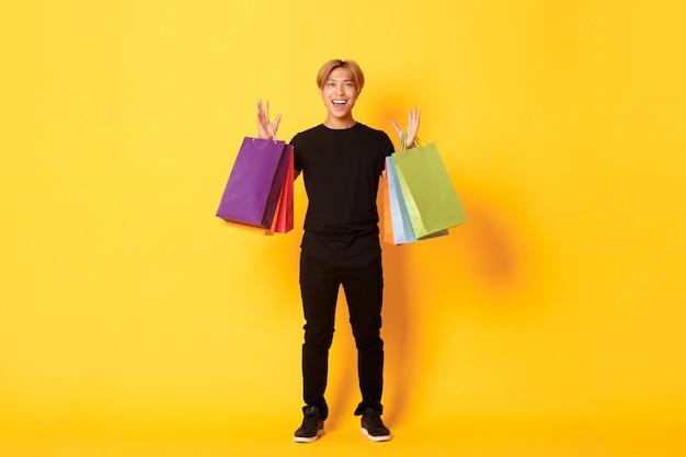 ショッピング、バッグを持って、笑顔、黄色の壁に幸せなハンサムなアジア人のフルレングス。
