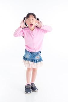 Во всю длину счастливой маленькой азиатской девушки крича над пробелом