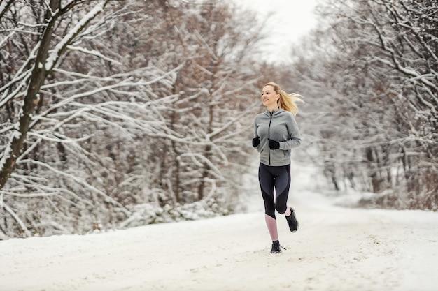 겨울에 눈 덮인 길에서 자연 속에서 달리는 행복한 중년 여성의 전체 길이입니다. 겨울 피트니스, 건강한 습관