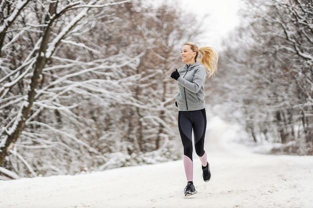 겨울에 눈 덮인 길에서 자연 속에서 조깅하는 행복한 스포츠우먼의 전체 길이입니다. 건강한 습관, 야외 피트니스, 겨울 피트니스