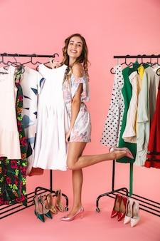 Полная длина счастливая женщина в платье, стоящая возле шкафа с одеждой и выбирающая, что надеть, изолирована на розовом