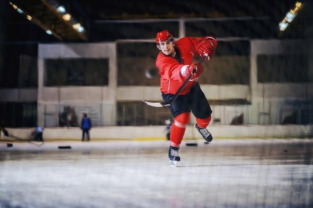 Хоккеист в полный рост стреляет по воротам в ледовом зале.