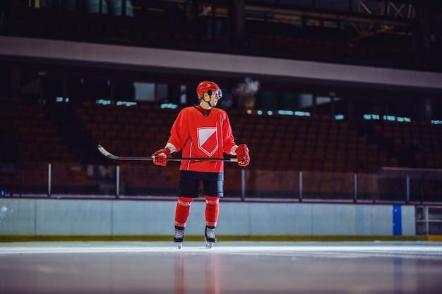 Хоккеист в полный рост стоит на льду с клюшкой в руках и ждет, пока товарищи по команде передадут ему шайбу.