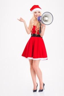 Полная длина радостной привлекательной блондинки в платье санта-клауса и шляпе с мегафоном, указывающим в сторону на белом фоне
