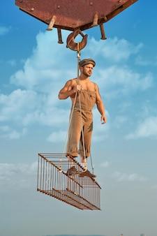 街の高いところにある鉄の建設物を持って立っている男の全長。帽子をかぶったビルダーと、目をそらしてポーズをとる作業着。クレーン保持構造。背景に雲と青い空。