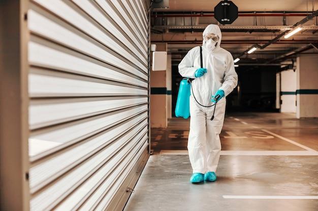 消毒剤付きの噴霧器を運び、ガレージを歩いている保護滅菌制服を着た男性の全身。