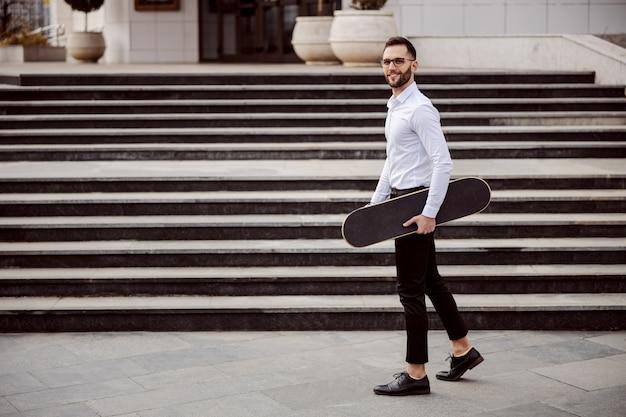 野外を歩いていると脇の下の下にスケートボードを持ってシャツを着た男の完全な長さ。