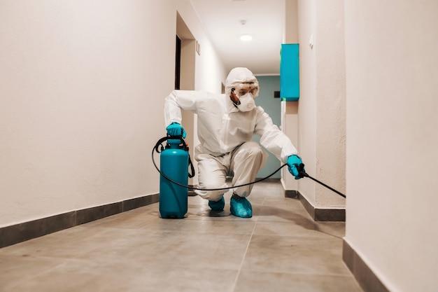 建物のホールを消毒する滅菌スーツを着た男の全身。コロナの概念からの保護。