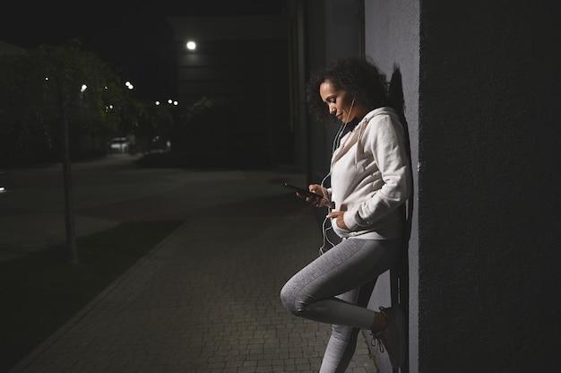 이어폰을 끼고 스마트폰을 확인하는 중년 히스패닉 여성, 도시 건물의 회색 벽에 기대어