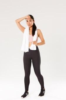Полная длина мотивированная, усталая спортсменка, азиатская фитнес-девушка с полотенцем, вытирающая пот во время тренировки, посещающая тренажерный зал, делая упражнения.