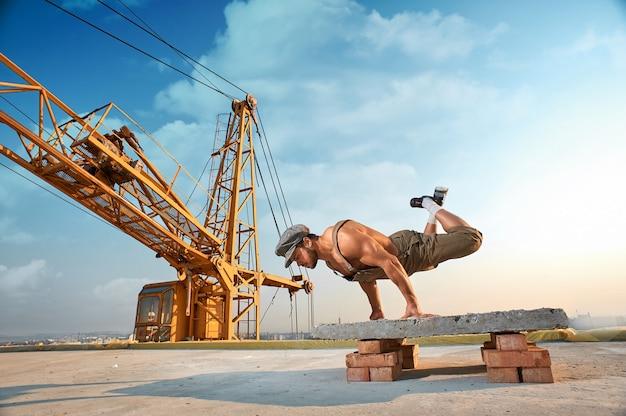 손에 운동을 하고 손에 팔 굽혀 펴기를 하는 근육질의 운동 남자의 전체 길이. 높은 건물을 마무리하지 않습니다. 배경에 큰 철 크레인입니다.