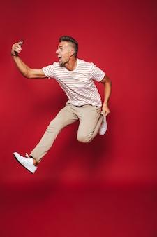 赤で隔離のスマートフォンでジャンプしてselfieを取る縞模様のtシャツの楽観的な男の完全な長さ
