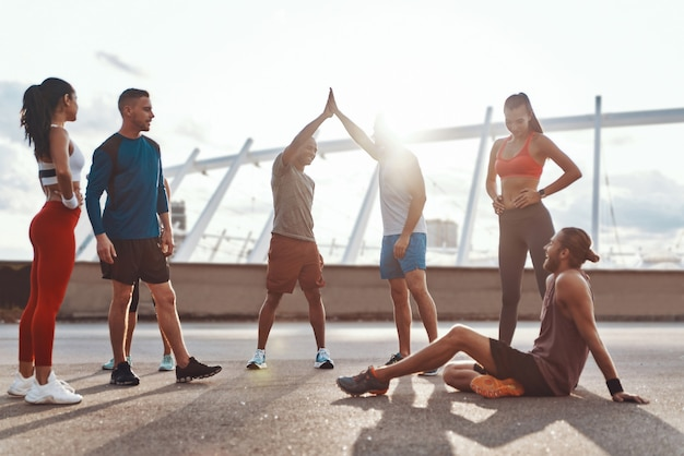 屋外で運動しながら互いに励まし合うスポーツウェアを着た全身の人々