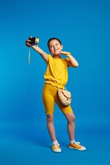 Полная длина позитивная девочка делает селфи с широко улыбающейся камерой