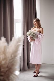 白い花を持って立って部屋の窓の外を見ているドレスを着たきれいな女性のフルレングス。ロマンチックなコンセプト。ライフスタイルのコンセプト