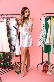 Полная длина красивая женщина в платье, стоящая возле шкафа с одеждой и выбирающая, что надеть, изолирована на розовом