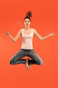 赤いスタジオの背景にジャンプしながら電話を取るかなり若い女性の完全な長さ。