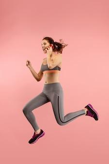 Полная длина красивой молодой женщины с мобильным телефоном во время прыжка Бесплатные Фотографии