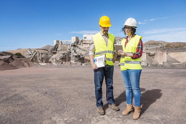 태블릿을 사용하고 산업 건설 현장에 서서 엔지니어링 프로세스를 논의하는 안전모 및 조끼를 입은 전문 남성 및 여성 엔지니어의 전체 길이