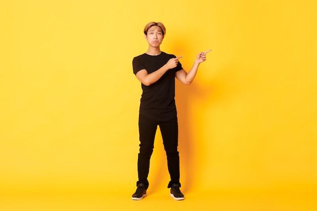 В полный рост грустный и несчастный азиатский парень в черной одежде