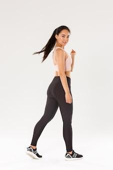 Полная длина нахальной красивой, стройной азиатской девушки, занимающейся фитнесом, атлетической женщины или тренера по тренировкам, идет с уверенным, мотивированным выражением лица, повернувшись в камеру с довольной улыбкой, белый фон