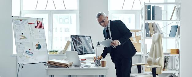 사무실에서 일하는 동안 디지털 태블릿을 사용하는 우아한 비즈니스 정장의 수석 상인의 전체 길이