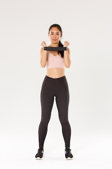 笑顔と断固としたスリムなブルネットのアジアフィットネスガール、抵抗コーチを伸ばしてエクササイズを示すトレーニングコーチの完全な長さは、トレーニング機器を示しています。