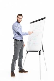 Улыбающийся бородатый элегантный мужчина в полный рост в очках делает презентацию, используя флипчарт и глядя
